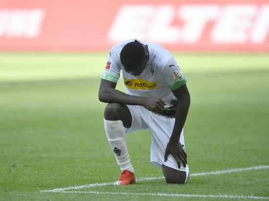 Marcus Thuram takes a knee after scoring in Bundesliga clash