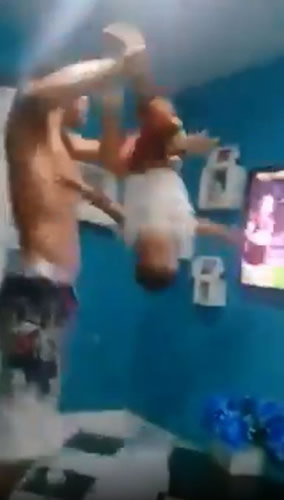 Outrage as Brazilian football fan swings son by the ankles while celebrating goal
